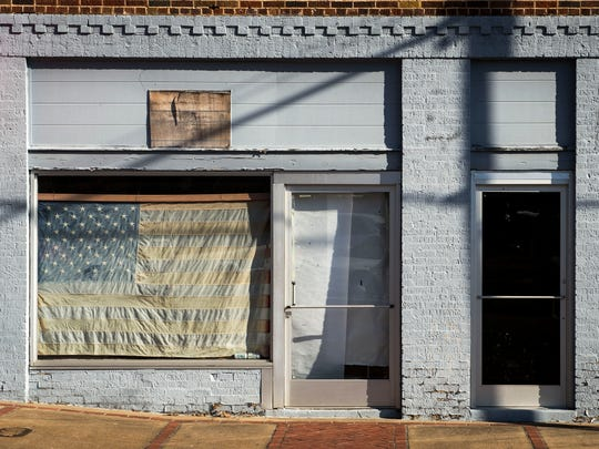 A sun-bleached American flag is seen on the window of a vacant storefront in Waynesboro, Tenn., on Nov. 14, 2016.