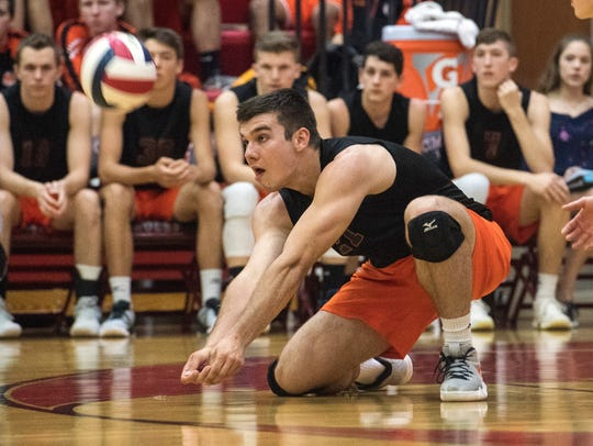 Northeastern's Cole Brillhart digs down for the ball,