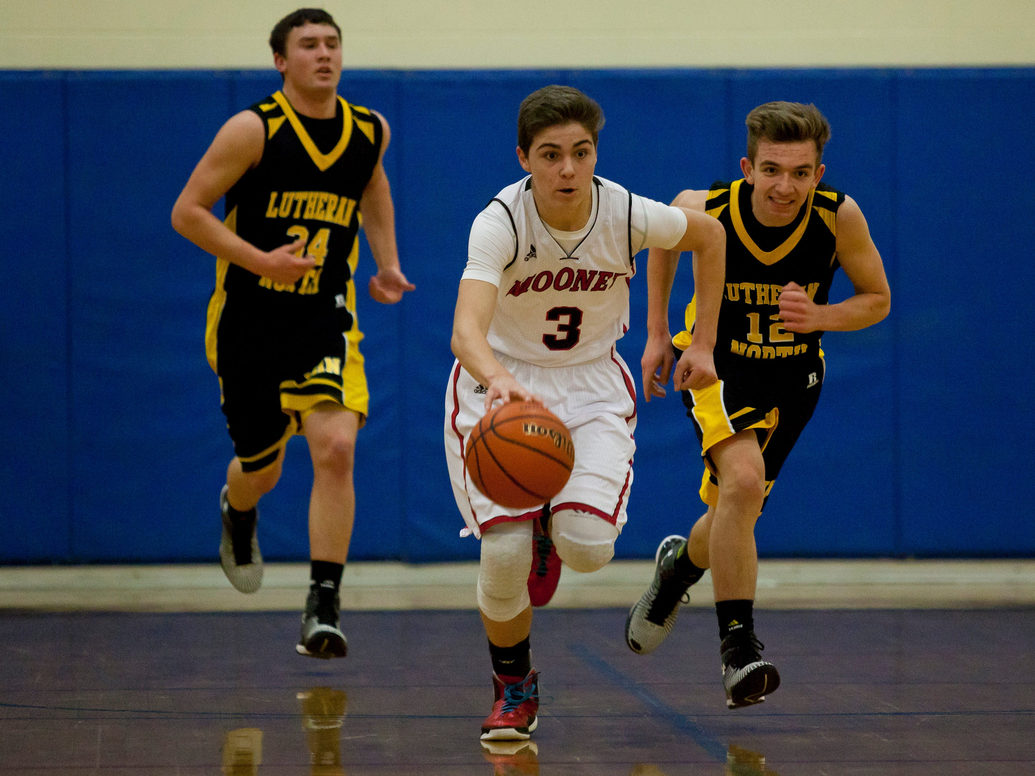 Cardinal Mooney freshman Daniel Everhart breaks away down court with the ball during a basketball game Tuesday, Feb. 17, 2015 at Cardinal Mooney High School in Marine City.