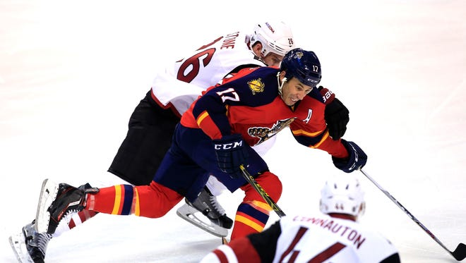 Feb 25, 2016: Florida Panthers center Derek MacKenzie (17) skates for the puck as Arizona Coyotes defenseman Michael Stone (26) and defenseman Kevin Connauton (44) defend in the second period at BB&T Center.