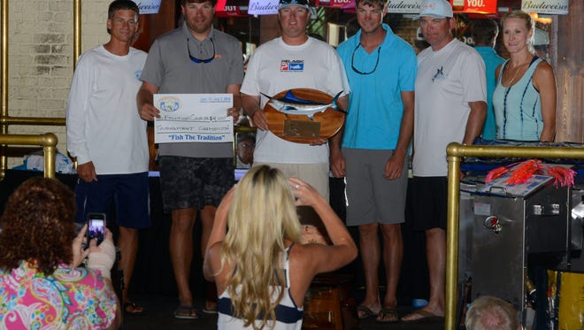 """Crew members of the Pensacola International Billfish Tournament champion boat """"Friction Course"""", get their photo taken during  the awards ceremony Sunday at Seville Quarter,"""