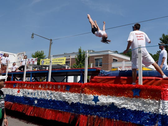 Liv Piatt does flips on top of the Olympic Academy Gymnastics float during the Granville Kiwanis Fourth of July Parade.