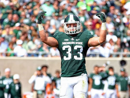 Michigan State linebacker Jon Reschke gestures to fans