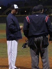 Alan Edmonson discusses a play with an umpire.