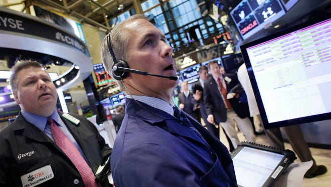 Traders monitor stock prices at the New York Stock Exchange.