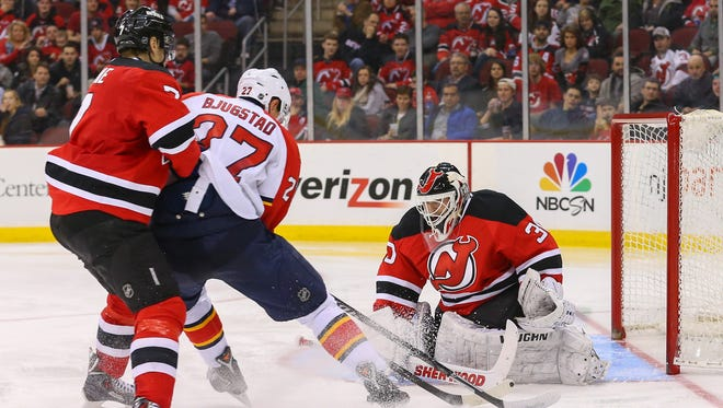 New Jersey Devils goalie Martin Brodeur (30) makes a save on Florida Panthers center Nick Bjugstad (27) while New Jersey Devils defenseman Mark Fayne (7) defends during the second period at Prudential Center.