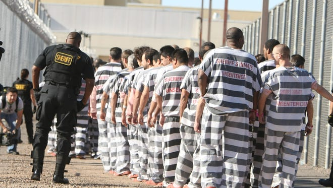 In this 2009 file photo, prisoners move to a new housing arrangement at  Lower Buckeye Jail, in Phoenix.