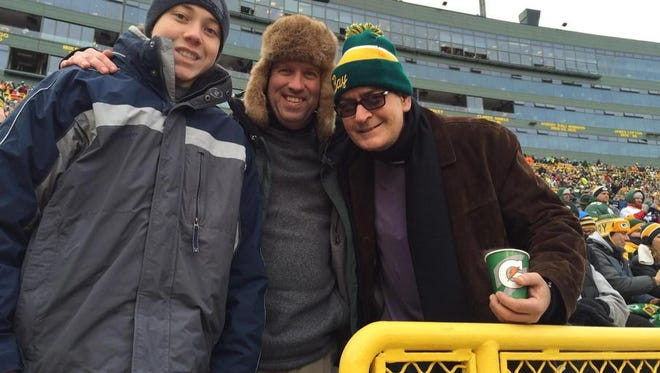 Paul Northway of De Pere, center, and his son, Andrew, left, pose for a photo with actor Charlie Sheen Sunday at the Dallas Cowboys-Green Bay Packers playoff game at Lambeau Field.