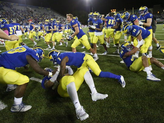 The Blue Hens, wearing their usual yellow uniform pants, celebrate a double overtime win against Richmond in 2017. The Hens worked out in blue pants Tuesday, a departure from the traditional Delaware uniform.