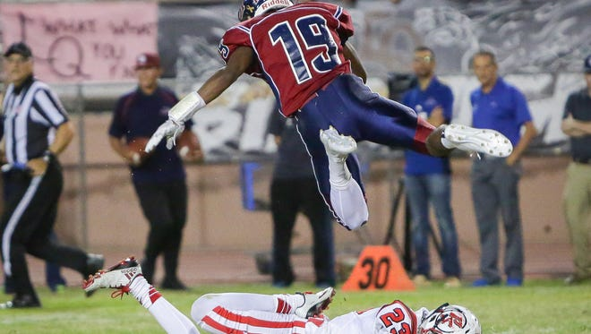 Derrick Kennedy jumps over a player after catching a short pass. La Quinta defeats Palm Springs, 38-14.