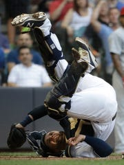 Brewers catcher Manny Pina is knocked over while tagging out the Cardinals' Kolten Wong at home during the third inning Tuesday night at Miller Park.