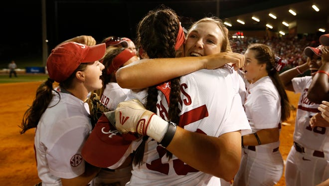 Alabama's Marisa Runyon, who hit a grand slam in the sixth during Game 3 of an NCAA softball Super Regional against Oklahoma, and Danae Hays (15) celebrate.