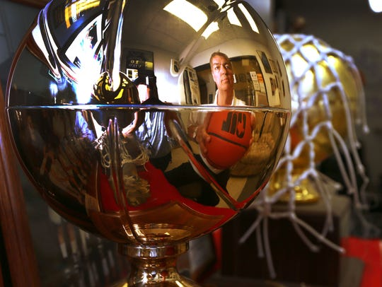 Richard Chacon is reflected in a championship trophy