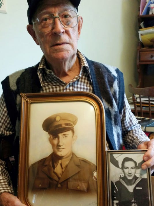 Carl McVitty holds a photo of his brother (left) along with a photo of himself.