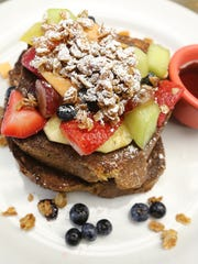 Tasty French Toast is piled high with fruit and granola