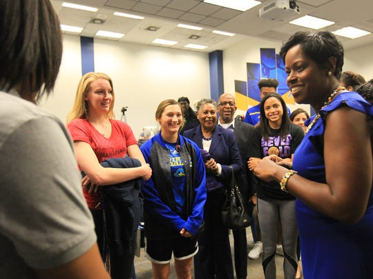 New University of Delaware women's basketball head coach Natasha Adair speaks with members of the team following an introductory press conference.