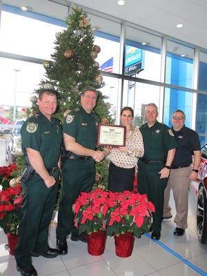 Maj. Douglas Hardie, left, St. Lucie Sheriff Ken Mascara, Tatiana Dyer, Capt. Adam Goodner, and Dyer General Manager Jonathan Holmes have their picture taken at the Dyer Difference Award presentation for December.
