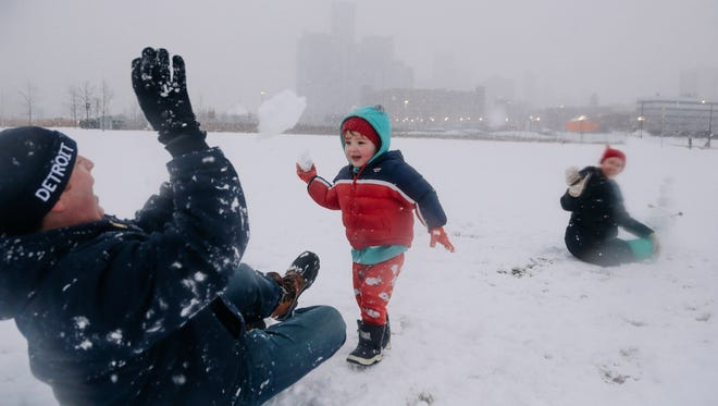 JD Gladstone, 2, of Detroit and his mother Anna Gladstone team up against his father Carl Gladstone while throwing snowballs on Tuesday January 31, 2017 at the William G. Milliken State Park in Detroit.