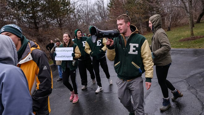 Eastern Michigan swimmer Logan Burton talks on a megaphone while marching with a small group of students and athletes to the University House following a rally to save Eastern Michigan University sports on Monday, April 17, 2018, outside the EMU Convocation Center in Ypsilanti.