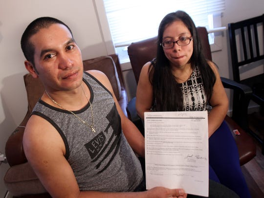 Carlos Larios holds an Order of Supervision form from the Department of Homeland Security during an interview with his wife Angelica Avila.