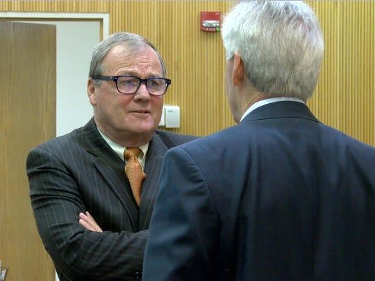 Raquel Garajau's attorney Robert Honecker (left) listens