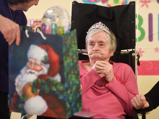Mildred Stoa receives a gift wrapped in a Christmas-themed bag during her 100th birthday party at Talahi Senior Campus Monday, Dec. 25, in St. Cloud.