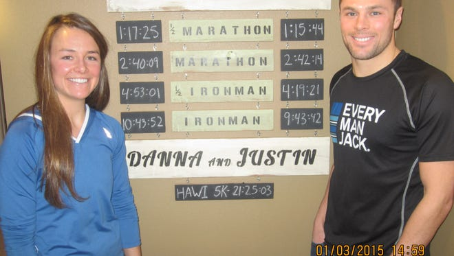 Justin Herrick, right, crafted a wood rack that highlights the fastest race times by he and his wife Danna (and their dog Hawi). It hangs in the Urbandale couple's basement.