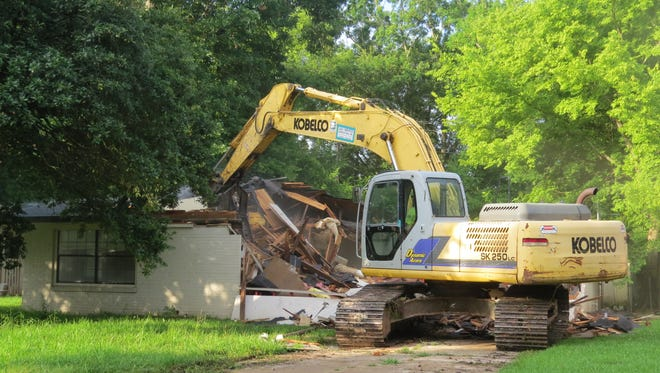 A track hoe demolishes a house in flood-prone Greenway Park subdivision as part of a flood-mitigation project.