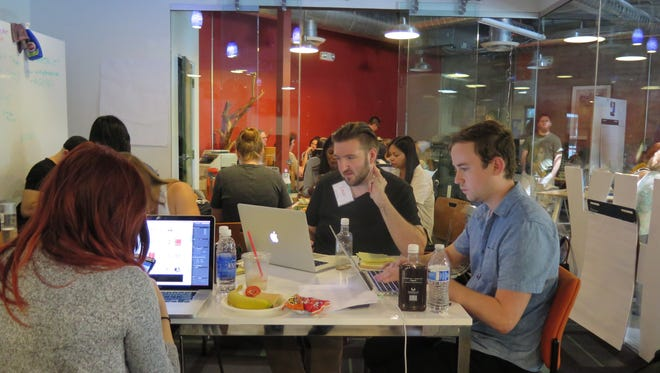 Volunteers work on creating marketing plans for local non-profits during the CreateAthon Phoenix event at CO+HOOTS on Saturday, Sept. 12, 2015.