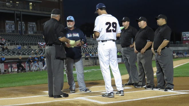 Patriots manager Brett Jodie (29) makes the Game 1 lineup exchange with Southern Maryland Blue Crabs manager Stan Cliburn as officials observe.