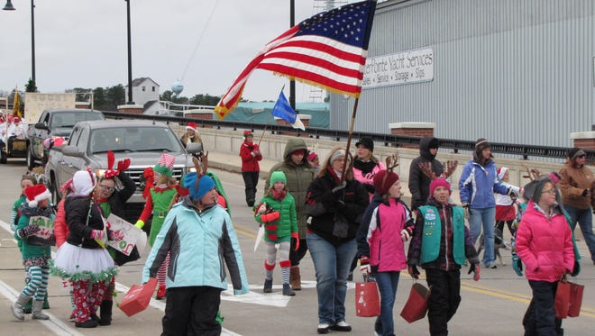 "Girl Scouts of Door County cross the Maple-Oregon Street Bridge during the Christmas by the Bay parade Saturday. The group won the ""best nonprofit entry"" award."