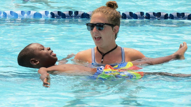 A Howard's Hope student floats in the former Murfreesboro YMCA pool with the help of swimming instructor Brittany Cagle in summer 2015.