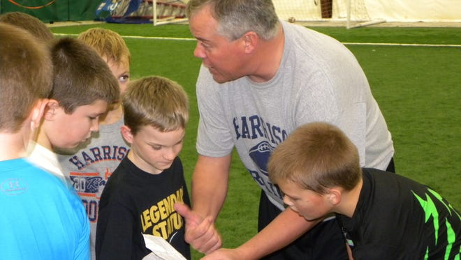 Coach Terry Peebles huddles with players (from left) Parker Golder, Cailix Dillon, Zach Bush, and Andrew Hardebeck during 5v5 passing football at Legacy Sport Center.