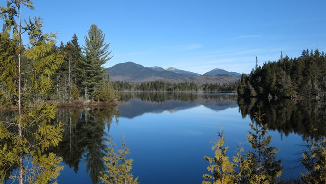 FILE--In this Nov. 17, 2015 file photo, Adirondack High Peaks, including snow-capped Mount Marcy, the state's highest summit, rear center, are reflected in Boreas Pond in North Hudson, N.Y. With his frequent trips to fish, boat and snowmobile in the Adirondacks, Gov. Andrew Cuomo has earned admiration from local leaders for his understanding of issues faced by the region's economically stressed hamlets. But some environmental advocates say his administration has placed local desires for easy recreational access ahead of wilderness protection, citing decisions favoring motor vehicles, bicycles and snowmobiles in recent additions to the 2.6 million acres of state-owned Forest Preserve.  (AP Photo/Mary Esch, File)