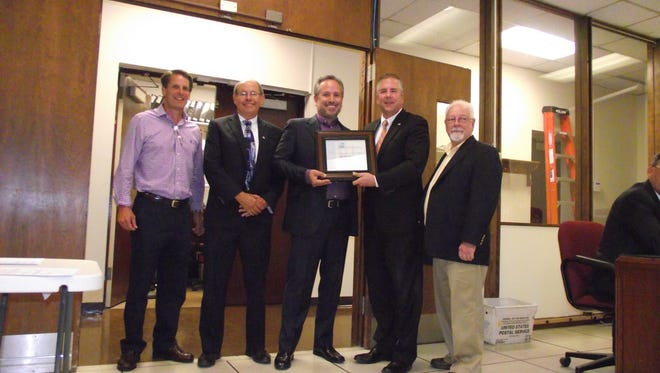 """Representatives of the New Jersey Chapter of the American Planning Association presented a commemorative plaque to Mayor Brian Gallagher at a recent borough council meeting in recognition of Downtown Somerville's designation by the organization as one of the state's """"Great Places."""" Participating in the presentation ceremony were, from left to right, Tom Genova, president of Downtown Somerville Alliance; Eric K. Snyder, Northwest representative of the state chapter, Charles Latini Jr., president of the state chapter, Gallagher, and Bernard Navatto, Somerville Planning Board chairman."""