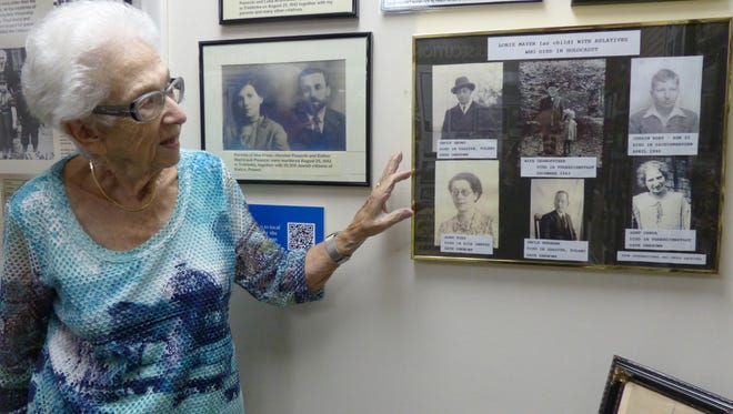 "Lorie Mayer, of Naples, points out family photos hung inside The Holocaust Museum & Education Center of Southwest Florida on Oct. 25, 2016. A holocaust survivor herself, Mayer has spent more than a decade working as a volunteer at the museum. She was recently honored when she was a recipient of the ""Daily Point of Light"" award."