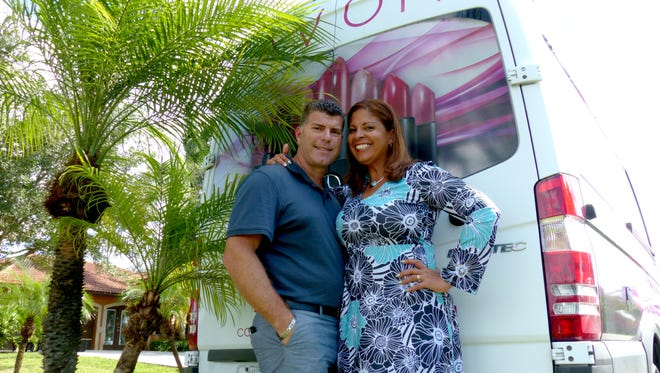 Carlos and Milagros Garcia pose with their Avon truck parked outside their home in East Naples.
