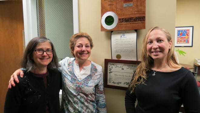 Millburn Green Team members Ellen Ingber, left, and Rene Paparian, center, with Green Schools leader and co-chair of the Essex County Environmental Commission Jennifer Duckworth happily post underneath the Sustainable Jersey award the proclamation honoring their work presented by the Township Committee Nov. 14.