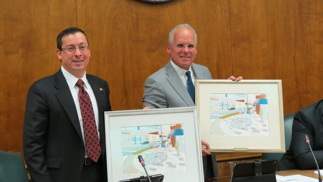 In their final meeting, Deputy Mayor Ian Mount, left, and Mayor Ted Bourke display gifts from the Downtown Millburn Development Alliance, artist renditions of the Complete Streets project they launched in 2016.