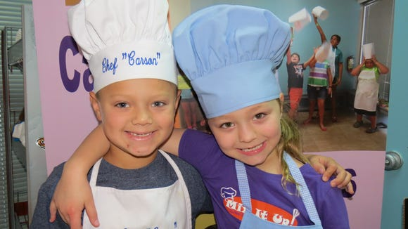 Carson Archer, left, and Farrah Sins are pictured during a cooking camp at Mix It Up in Houma. The cooking class business will soon have a location in Lafayette.