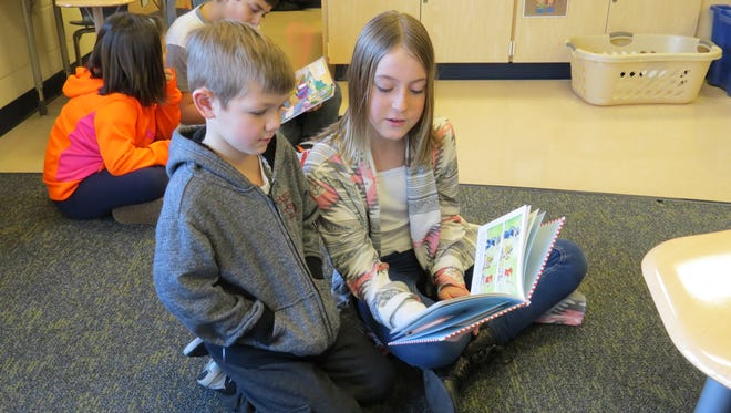 Kindergarten student Noah Rickey enjoys a story read by fifth-grade student Kaylie Simpson during the Reading with Redskin Rock Stars reading program at Bataan Memorial.