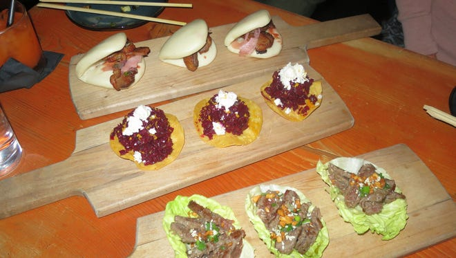The Edibles, or small plates, are served on wooden paddles. Here (front to back), elk lettuce wraps, beet and mushroom tostadas with goat cheese, and duck steamed buns are served.