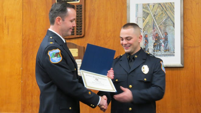 Millburn Police Officer Donald Royce, right, receives a citation from Police Chief Brian Gilfedder for heroically saving a woman from a burning car on Jan. 1.