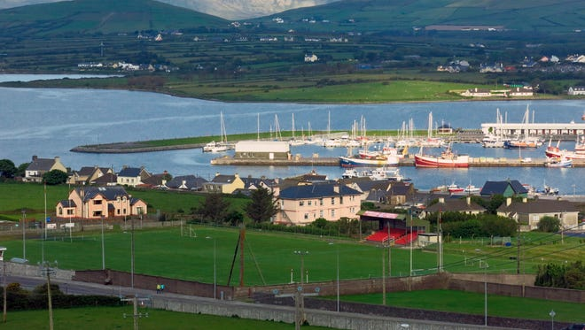 This May 25, 2016 photo shows boats in the harbor against a backdrop of lush, rolling hills in Dingle, Ireland. The town on Ireland's southwest coast has a lively pub scene.