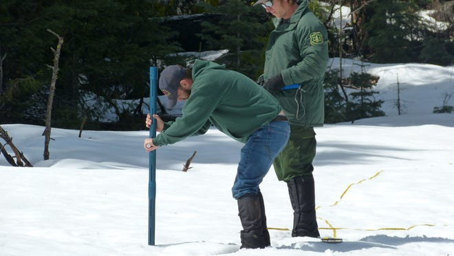 Matthew Herndon, left, and Sean Stalie take a snow sample Monday at Big Springs within the Lassen National Forest.