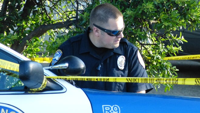 A Redding police officer takes down a report about Monday morning's shooting at a Mistletoe Lane home.