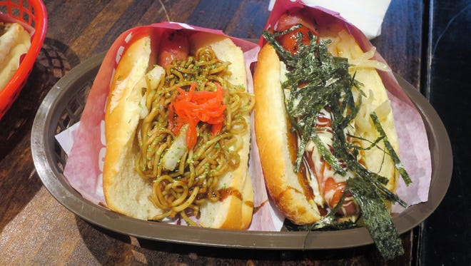 The Arabiki pork hot dog topped with yakisoba noodles (left) and the bestseller, the Kurobuta Terimayo (right), are two popular Japadog specialties.
