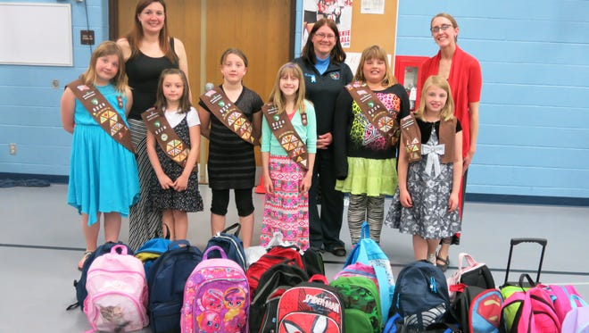 Girl Scouts from Monroe Elementary in Manitowoc used funds from cookie sales and donations to provide 21 backpacks for children in foster care. Pictured are, front, from left: Gianna Behnke, Kerigan Halada, Lydia Emond, Rose Benzinger, Kadence Brasted and Olivia Herrman; and back, from left: Angie Behnke, co-leader troop No. 8226, Karen Zahn, foster care administrator for Manitowoc County, and Jenny Gleichner, troop organizer for Monroe Elementary/co-leader troop No. 8226. Not pictured is Nevaeh Barton.