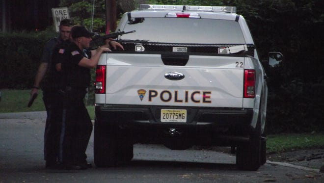 Police officers position themselves behind a police truck on Leonard Place in Ridgewood.