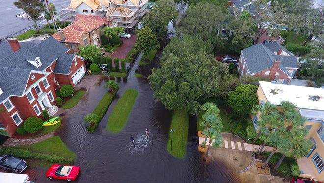 People trudge through floodwaters in the aftermath of Hurricane Irma in Jacksonville, Fla.